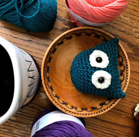 Owl in a wooden bowl surrounded by yarn and a coffee mug