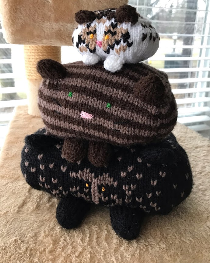 Three knit cats stacked on top of each other. All a different size and pattern.