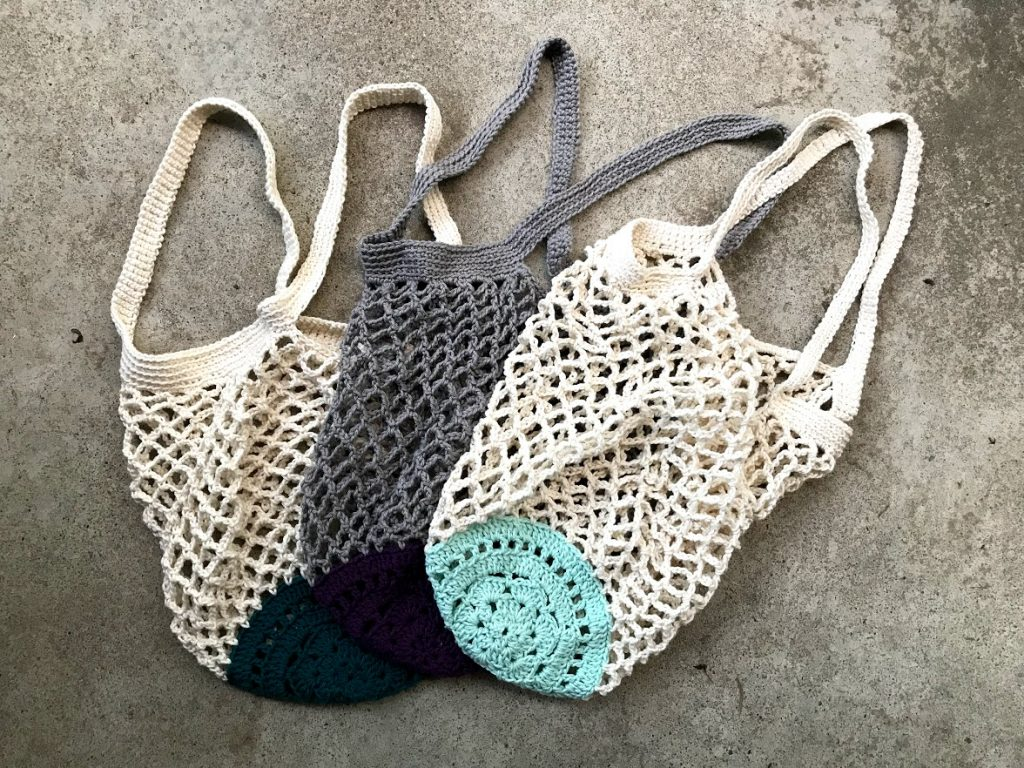 3 Crochet market bags pictured with 3 different coloured bottoms. Aqua, turquoise and purple.