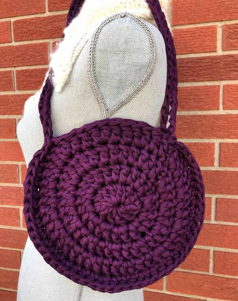 crochet circle purse on a mannequin